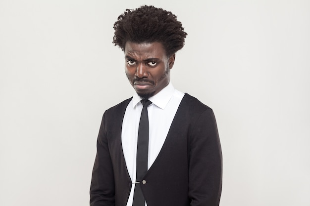 Dramatic afro man cry and looking at camera. studio shot, gray background