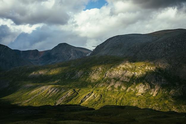 햇빛 아래 높은 산 벽과 흐린 하늘 아래 그림자가 있는 극적인 고산 풍경. 고원의 변화무쌍한 날씨가 있는 아름다운 산 풍경. 화창하고 흐림. 햇빛과 그림자.