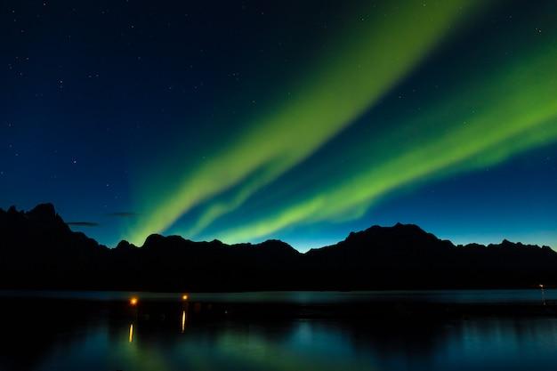 北ヨーロッパ-ロフォーテン諸島、ノルウェーの山の上の劇的なオーロラ、極光、