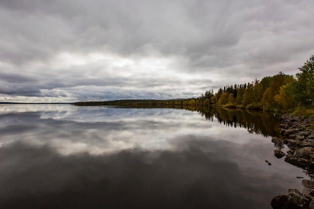 Dramatic autumn clouds reflection in muonio lake, lapland, northern finland Premium Photo