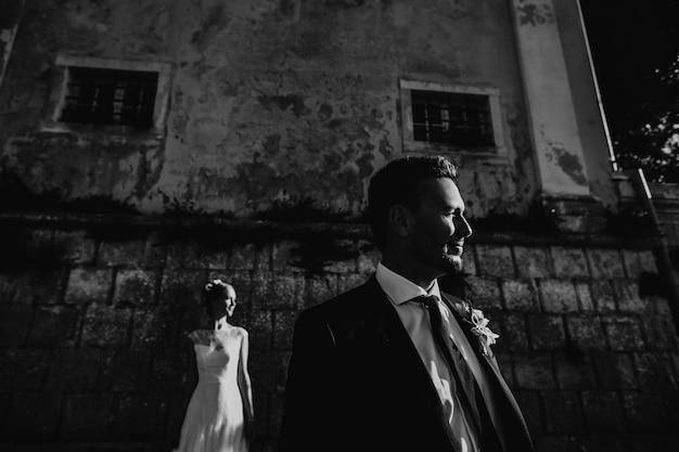 石の壁の前にポーズを取る結婚式のカップルの劇的な黒と白の写真