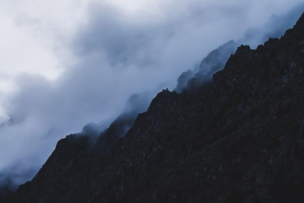 Dramatic bleak fog among giant rocky mountains.ing.