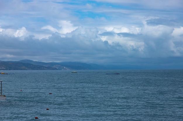 黒海のビーチの劇的なぼやけた山の風景、雲と空のある風景が水に映っています。