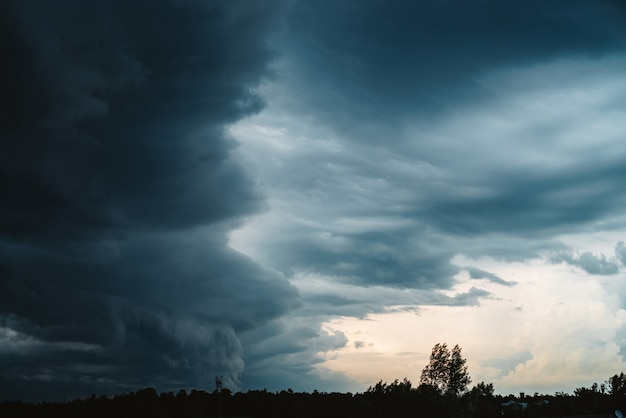 Dramatic cloudscape. sunny light through dark heavy thunderstorm clouds before rain. overcast rainy bad weather. storm warning. natural blue background of cumulonimbus. sunlight in stormy cloudy sky.