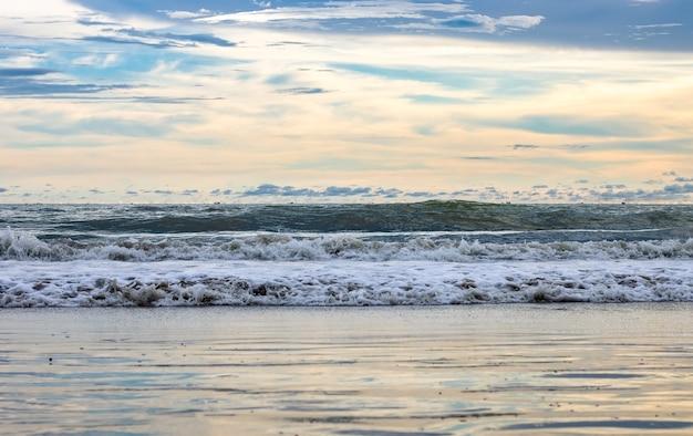 하늘 반사와 파도와 바다 해변에서 저녁 전에 극적인 흐린 하늘