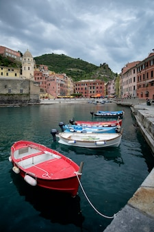 Dramatic cloudy sky over vernazza harbor, with some boats in the foreground. cinque terre, italy.