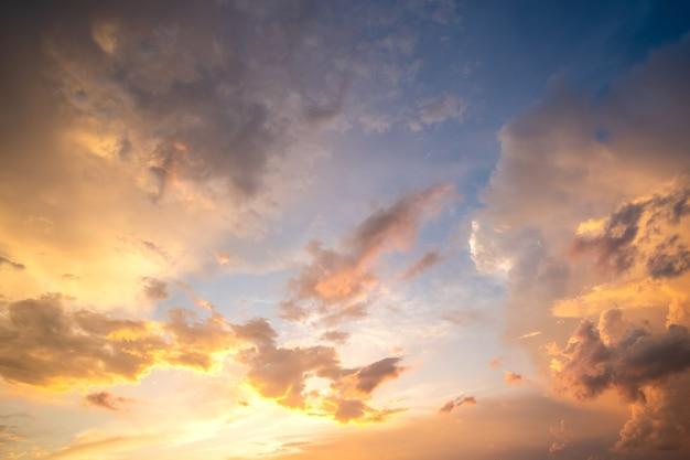 オレンジ色の夕日と青い空に照らされたふくらんでいる雲と劇的な曇りの日没の風景
