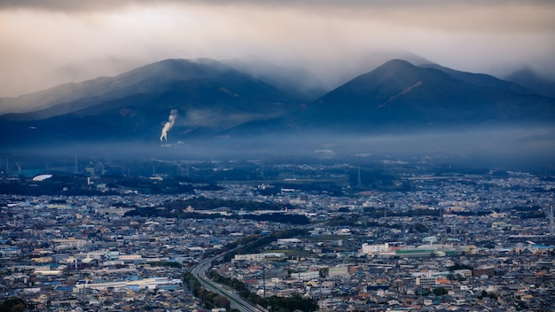 Dramatic and dark process cityscape in strom and smog layer mountain background in japan
