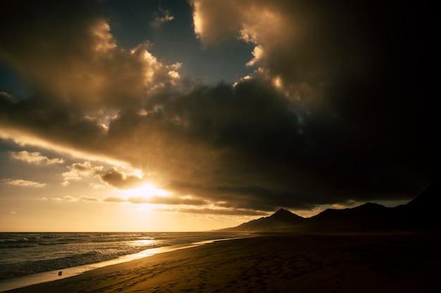 劇的な暗い影が背景に黒い山とビーチに沈む-冒険の概念のための太陽と海-風光明媚な風景と雲と美しい空