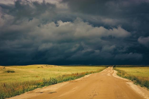 劇的な暗い嵐の雲と地平線への日光の未舗装の道路