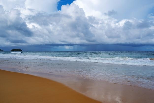 푸켓 섬의 고요한 해변에서 바라본 해안선을 따라 바다 너머 멀리서 비가 쏟아지는 바다 위의 극적인 어두운 폭풍 흰 구름 환경 기후 변화 개념