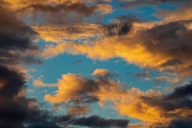 Dramatic fluffy cloud illuminated by disappearing rays at sunset dark thunderclouds across blue sky