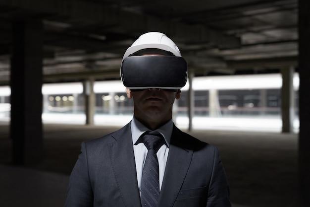 미래의 프로젝트를 3d로 시각화하면서 건설 현장에서 vr 장비를 착용 한 사업가의 극적인 정면 초상화,