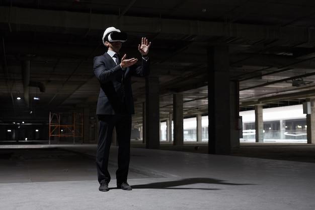 미래의 프로젝트를 3d로 시각화하면서 건설 현장에서 vr 장비를 착용 한 사업가의 극적인 전체 길이 초상화,