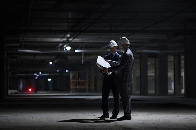 건설 현장에서 어둠 속에서 서있는 동안 hardhats를 착용하고 계획을 잡고 두 비즈니스 사람들의 극적인 전체 길이 초상화,