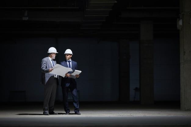 가혹한 조명으로 불이 켜진 건설 현장에서 어둠 속에 서있는 동안 hardhats를 착용하고 계획을 잡고 두 성숙한 비즈니스 사람들의 극적인 전체 길이 초상화,