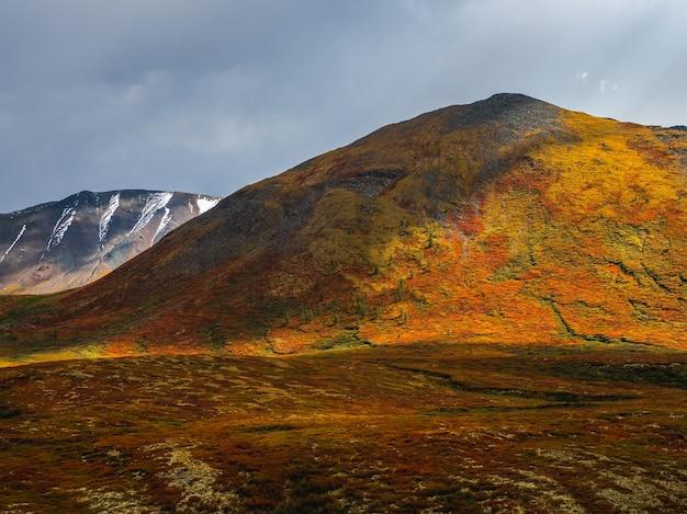 Драматический золотой свет и тень на скале в осенней степи. высокогорное плато ештыколь. горный алтай, россия. сибирь.