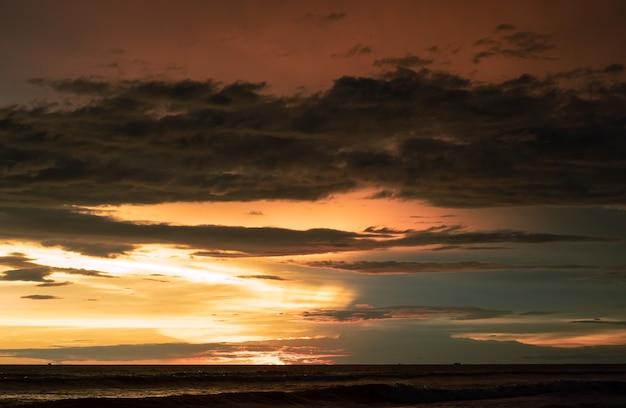 바다 위에 일몰 순간에 극적인 황금 하늘