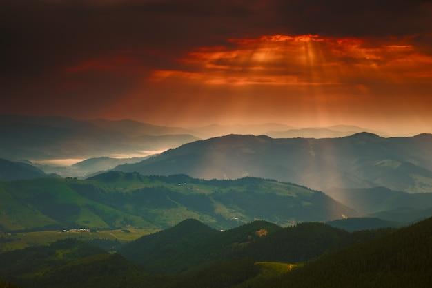 Драматическое золотое закатное небо с солнцем и горными карпатами