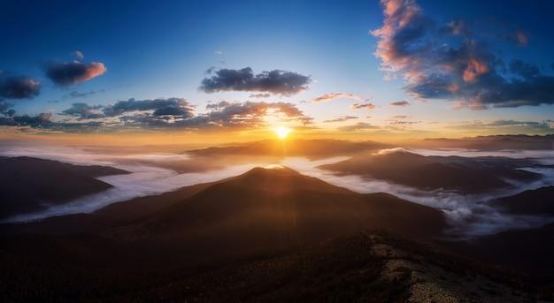Драматический пейзаж в карпатах с утренним туманом в долине и красивым небом на восходе солнца.