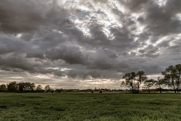 Драматический пейзажный вид с солнечными лучами, сияющими сквозь темное облачное небо