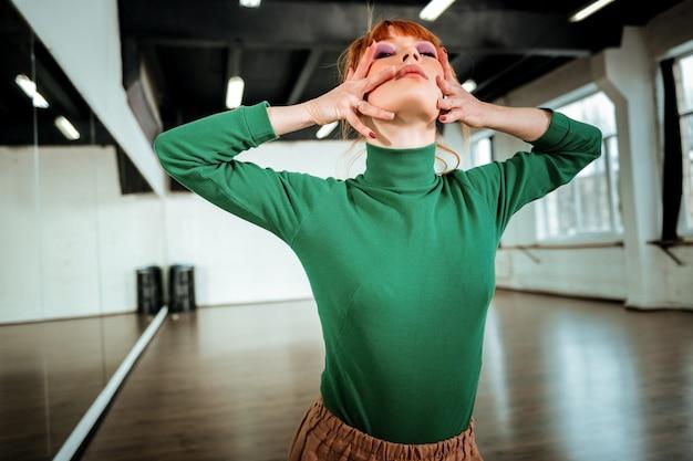Эффектный вид. молодая рыжеволосая учительница танцев с ярким макияжем выглядит эффектно во время танцев в студии