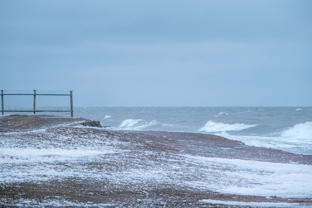 Dramatic minimalistic seascape with old fence and waves with white foam on the white sea.