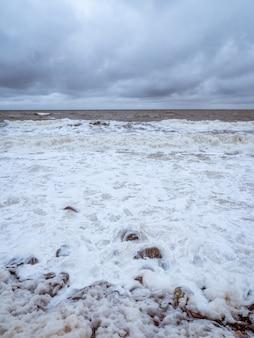 하얀 바다에 파도와 하얀 거품이 있는 극적인 최소한의 바다 경치.