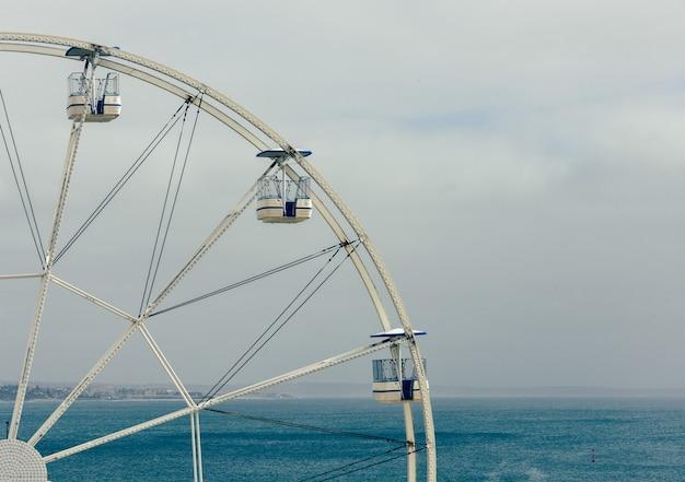 Драматический мрачный снимок колеса обозрения в кашкайше, португалия, на фоне туманного неба