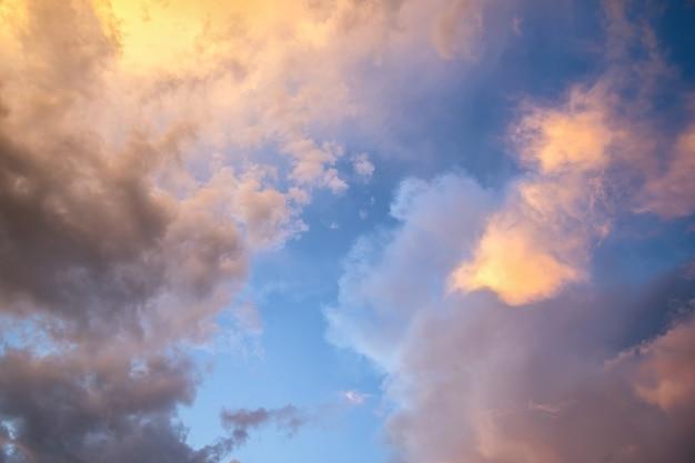 黄色の夕日と青い空に照らされたふくらんでいる雲と劇的な不機嫌そうな夕日の風景。