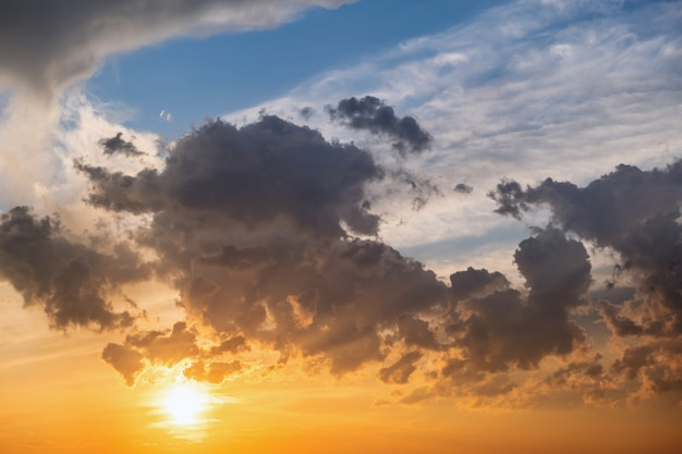Dramatic moody sunset landscape with puffy clouds