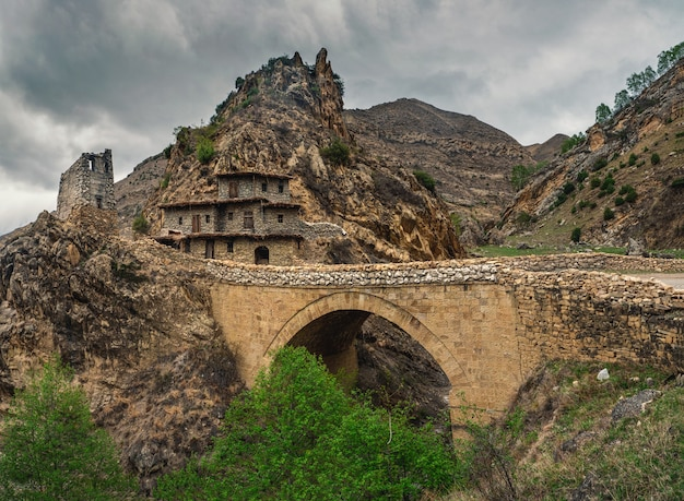 暗い雨の日の古い石の橋と劇的な山の風景。ダゲスタン。