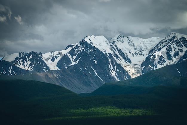 どんよりした天気で太陽に照らされた森の上に大きな雪の山の尾根がある劇的な山の風景。鉛の灰色の雲と森の日光の下で高い山脈のある大気中の高地の風景。
