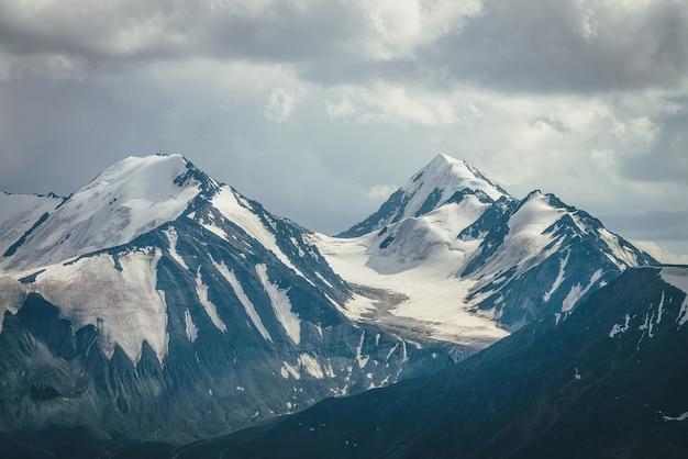 흐린 하늘 아래 큰 눈 덮인 산 능선과 극적인 산 풍경. 흐린 날씨에 높은 산맥이 있는 어두운 대기의 고원 풍경. 회색 구름 아래 멋진 큰 산.