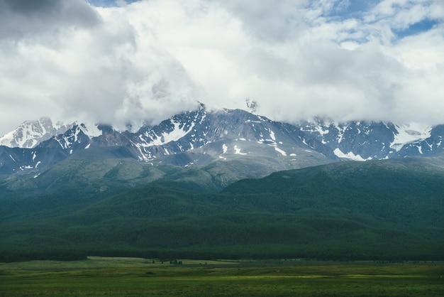 低い雲の中に雪に覆われた山脈のある劇的な山々の風景。どんよりした天気で緑の森の上に高い山の尾根がある大気の高地の風景。山の壁の素晴らしい景色。