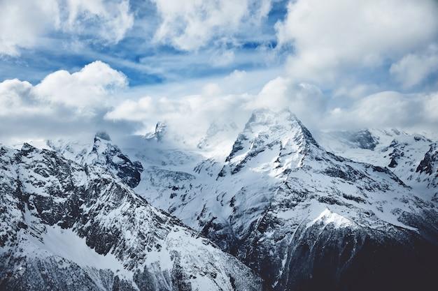 겨울철에 흐린 하늘 아래 눈 덮인 높은 산의 극적인 파노라마 야생 자연 사진