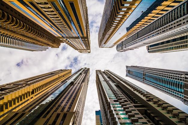 Драматическая перспектива с низким углом обзора небоскребов, смотрящих в небо, дубай. крайний предел; точка схода