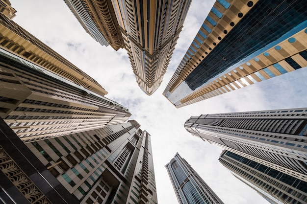 Dramatic perspective with low angle view of skyscrapers looking up to the sky, dubai. vanishing point