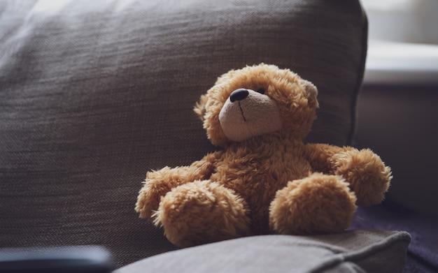 Dramatic photo of teddy bear is sitting on sofa in dark room with sunlight shining.