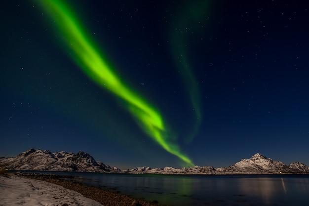 劇的な極光、ヨーロッパ北部-ロフォーテン諸島、ノルウェーの山の上のオーロラ