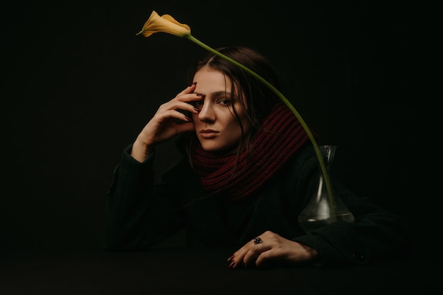 Dramatic portrait of a girl in a coat and scarf with a flower in the vintage style