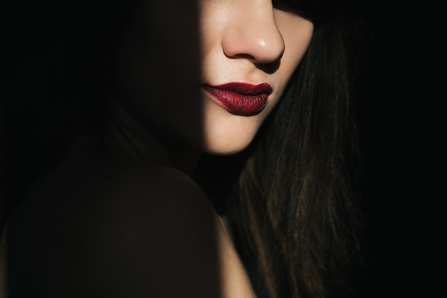 Dramatic portrait of a girl with red lipstick on her lips