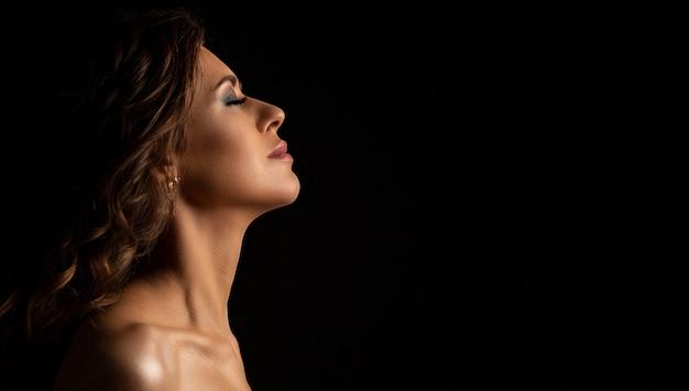 スタジオでポーズをとる完璧なメイクと裸の肩を持つ素敵なブルネットの日焼けモデルの劇的な肖像画。テキスト用のスペース