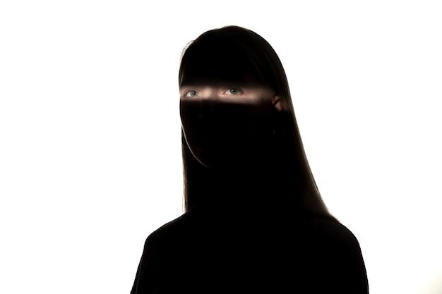 白いスタジオの背景に分離された暗闇の中で白人の若い女の子の劇的な肖像画。暗い顔に日光のライン。人間の本性、隠されたもの、心理学の概念。アートエレガントなクリエイティブな写真。