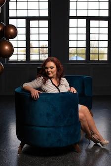 Драматический портрет милой зрелой рыжеволосой женщины, сидящей на бархатном диване в комнате с большими окнами