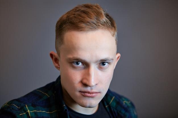 濃い灰色の壁に白い青い目の男性の劇的な肖像画。