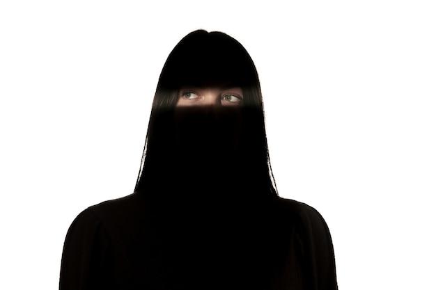 Драматический портрет молодой девушки в темноте, изолированные на белой стене студии