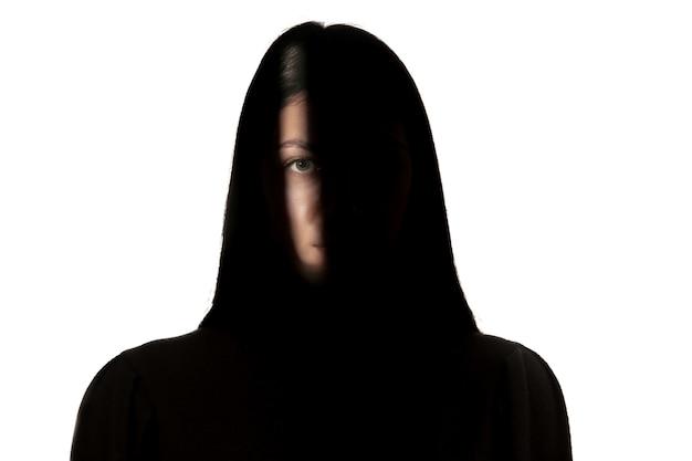 白いスタジオの壁に分離された暗闇の中で若い女の子の劇的な肖像画