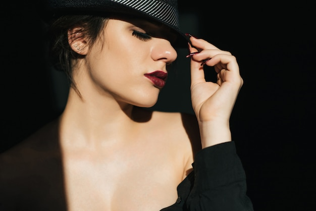 Dramatic portrait of sexy young girl in black hat with red lipstick