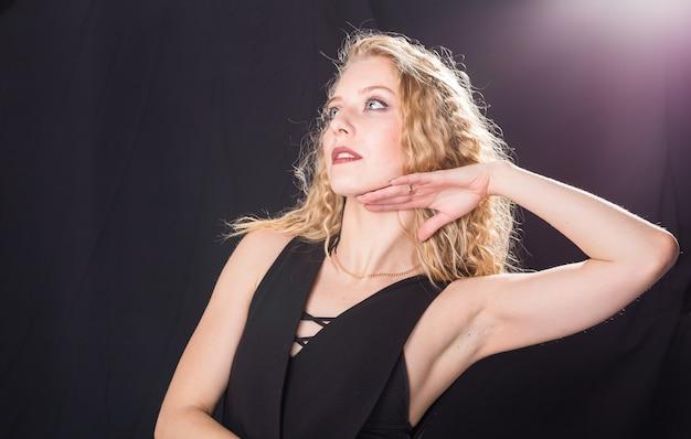 검은 바탕에 곱슬머리를 한 아름다운 금발 여성의 극적인 포즈.